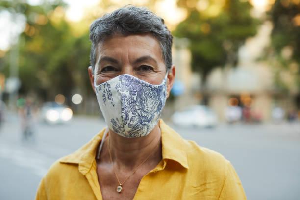 Eine Frau im mittleren Alter, die eine Schutzmaske trägt und lächelt – Foto