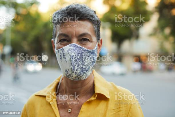 One Midle Aged Woman Wearing A Protective Mask And Smiling Stock Photo - Download Image Now