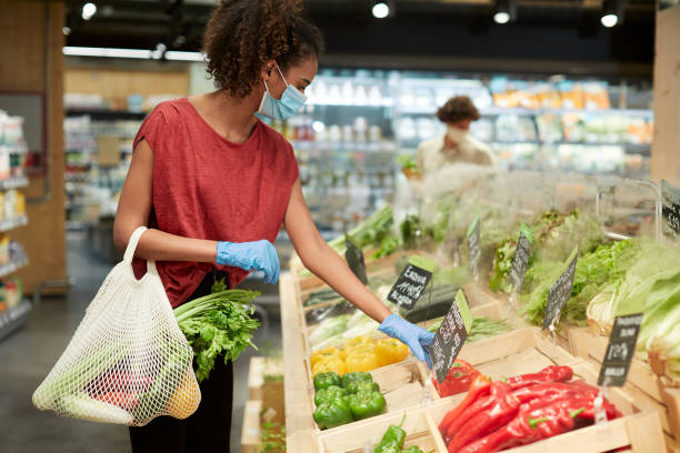 um cliente milenar escolhendo vegetais em um supermercado. - costumer - fotografias e filmes do acervo