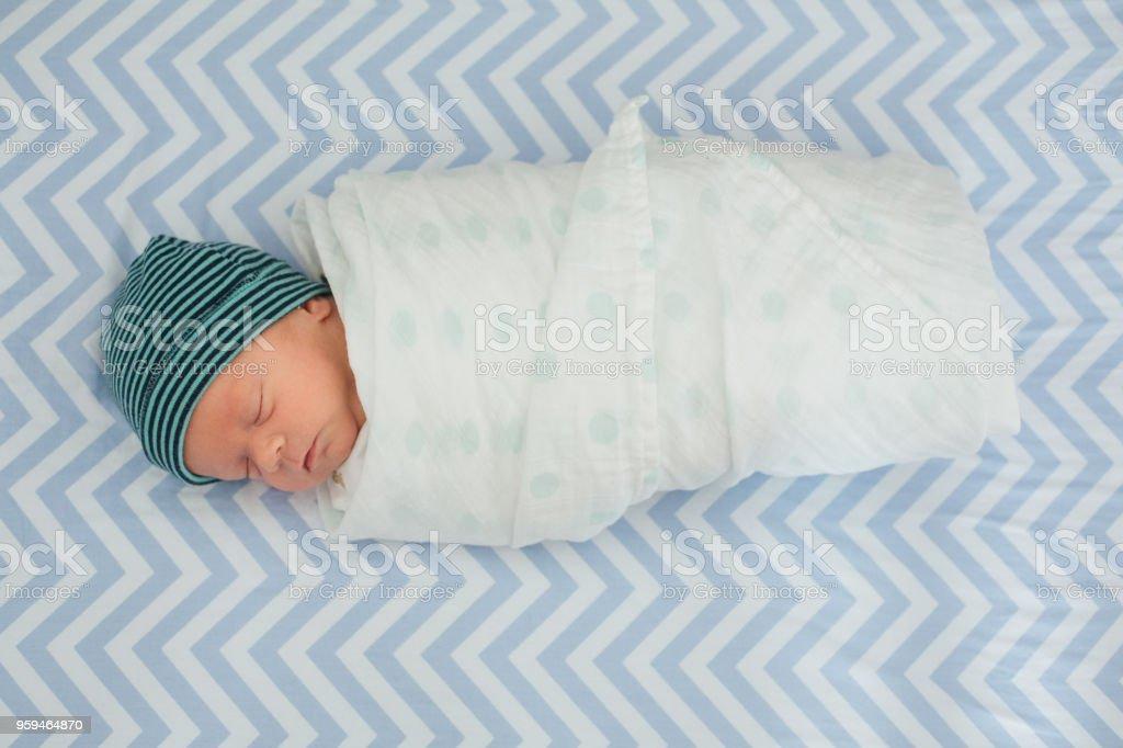 Één maand oude baby gewikkeld in een deken swaddle foto