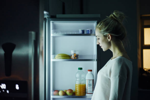 One more snack before bed Shot of a young woman opening the fridge at night in her home fridge stock pictures, royalty-free photos & images