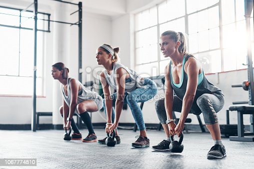 Shot of three women working out with weights at the gym