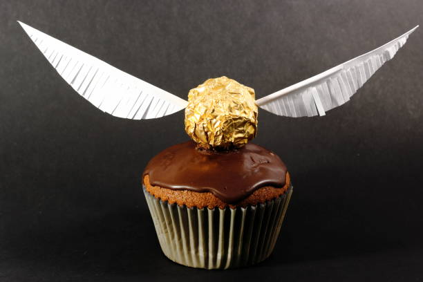 One muffin with Golden Snitch decoration on black background. Harry Potter theme. stock photo