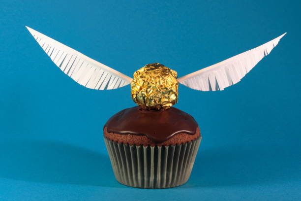 One muffin with Golden Snitch decoration on blue background. Harry Potter theme. stock photo