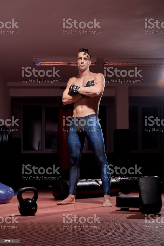 one muscular boxer posing, low angle view, boxing equipment, room indoors. stock photo