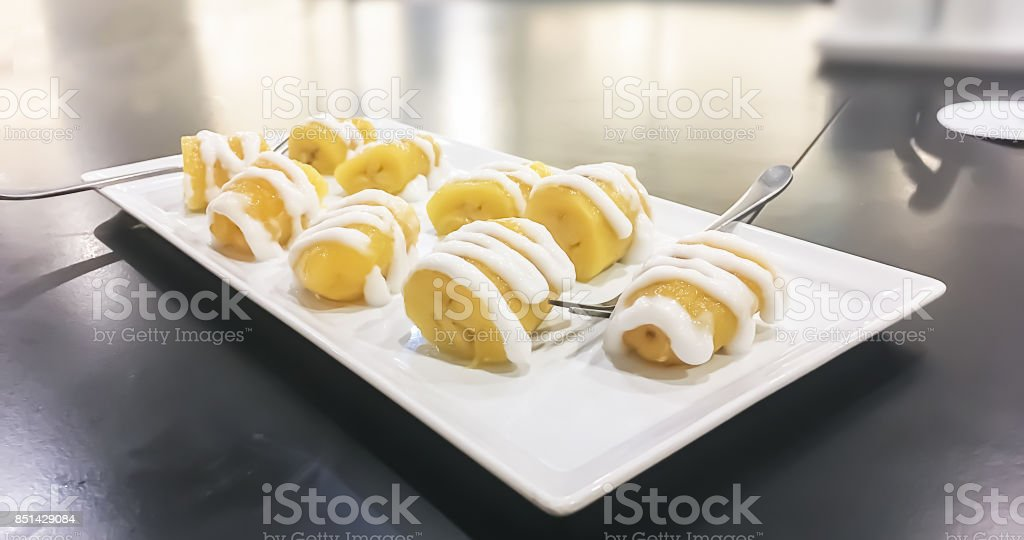 One of Exotic popular Thai dessert is Boiled bananas in syrup with coconut milk on top. stock photo