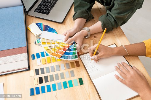 One of young female designers holding color palette over table while her colleague making notes during work over new order
