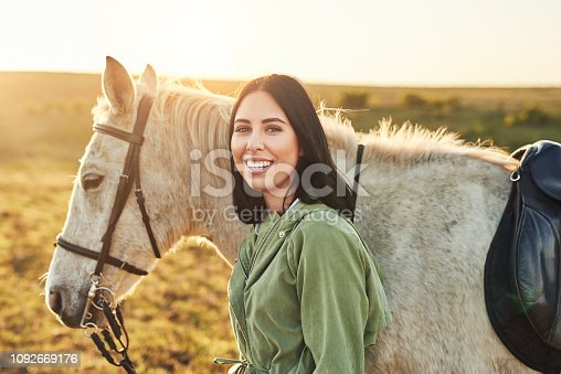 Shot of a young woman spending time with her horse on a farm