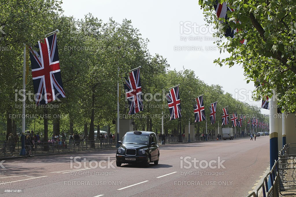 London taxi driving down the Mall with Union Jack flags stock photo