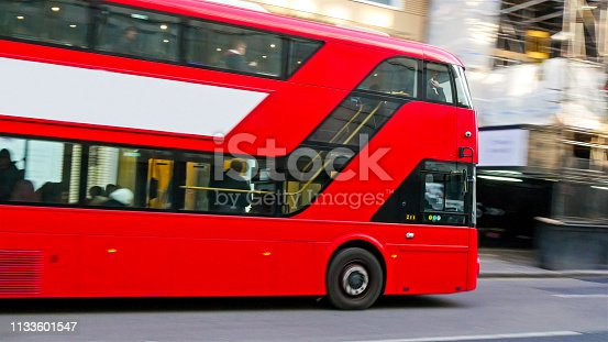 One of Londons red bus passing by the street. It is a big bus with 2 floors on it.