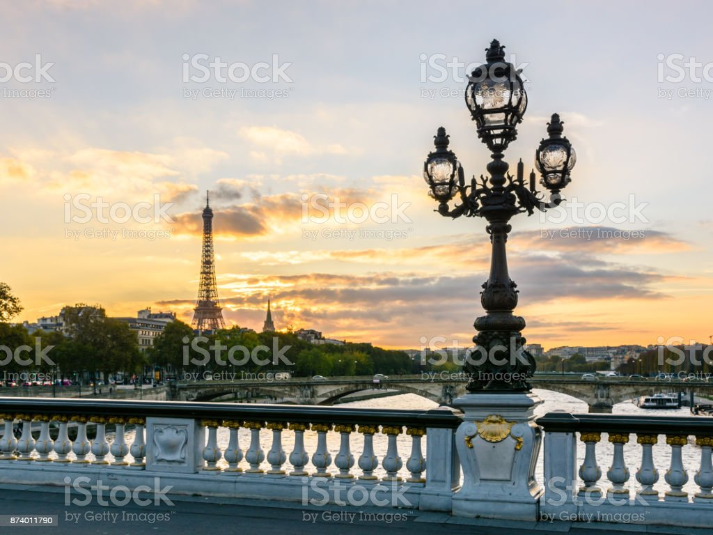 One of the Art Nouveau style street lights of the Alexander III bridge in Paris with the Eiffel Tower in the background at sunset stock photo