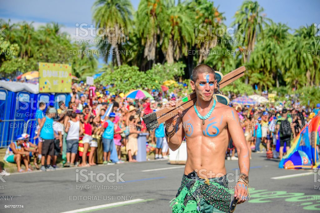 One of the artist of Bloco Orquestra Voadora walking with naked torso carrying his stilts on his shoulder, Carnaval 2017 stock photo