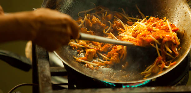 one of the most favorite and famous asian thai street fast food in hot pan, pad thai, is a stir fried rice noodle dish commonly served as a street food and at casual local eateries in thailand. - peanut food stock photos and pictures
