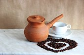 One old brown clay Turk for cooking Turkish coffee, white clean Cup and saucer and roasted coffee beans in the shape of a heart on the table