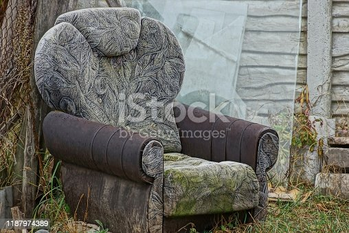 one old dirty chair stands outside in the grass against the wall