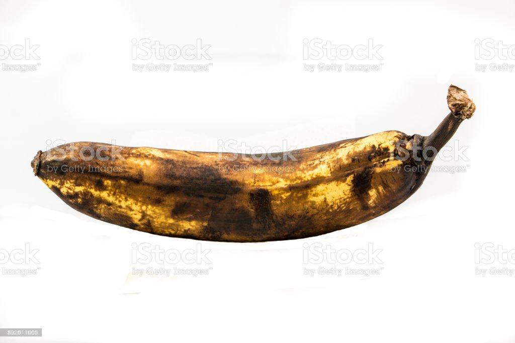 Eine ältere braune Banane mit weißem Hintergrund – Foto