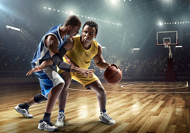 One on one basketball game in the spotlight Low angle view of a professional basketball game. A player is trying to block  the opposite team player with a ball. A game is in a indoor floodlit basketball arena. All players are wearing generic unbranded basketball uniform. jump shot stock pictures, royalty-free photos & images