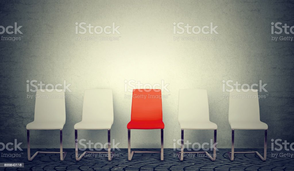 One opening for the job business concept. Row of white chairs and one red in the middle stock photo