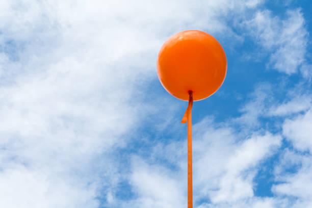 ein orangefarbener ballon, der in den blauen himmel fliegt - hochzeitsreise amsterdam stock-fotos und bilder