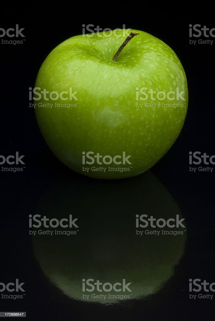 One Organic Granny Smith Apple on Reflective Black royalty-free stock photo