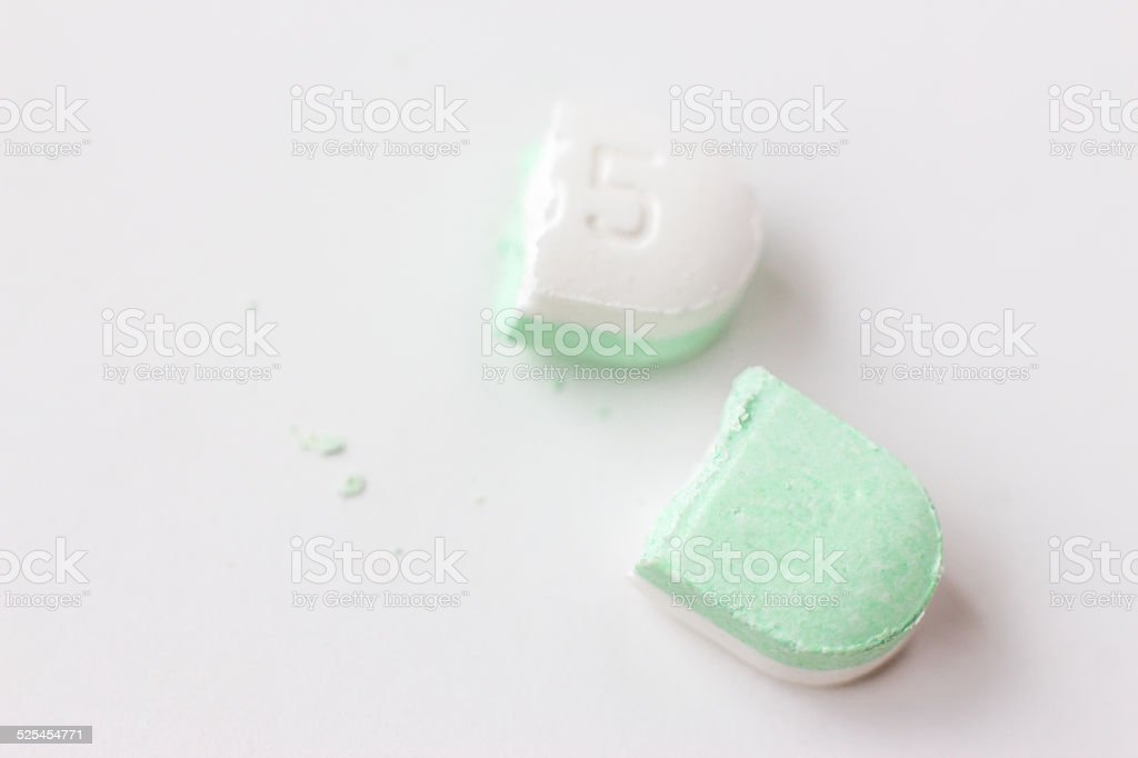 one oval pill cut in half on white background. stock photo