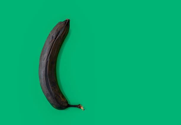 One overripe banana isolated on green background One overripe banana isolated on green background addle stock pictures, royalty-free photos & images