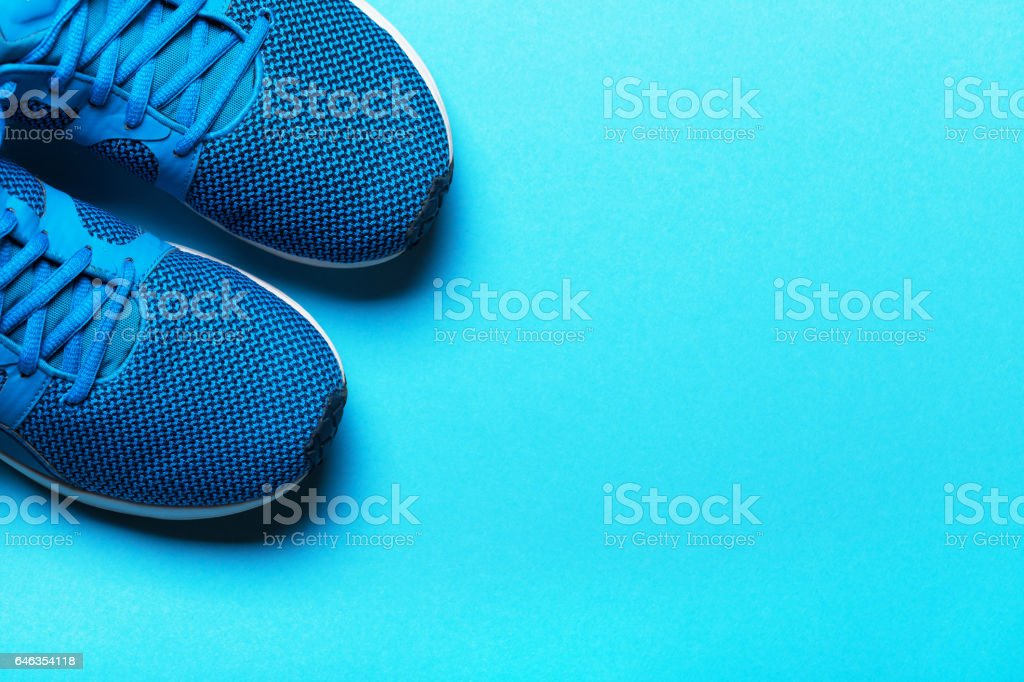 One Pair of blue sport shoes on blue background. stock photo