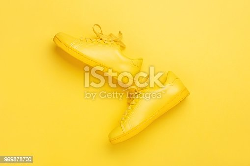 Pair of yellow shoes on yellow background. Trendy summer color, monochrome image with copy space. Hipster concept.