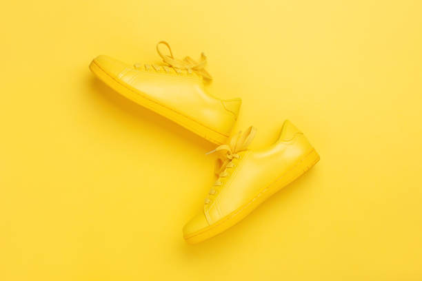 one pair of yellow shoes on yellow background. - yellow stock photos and pictures