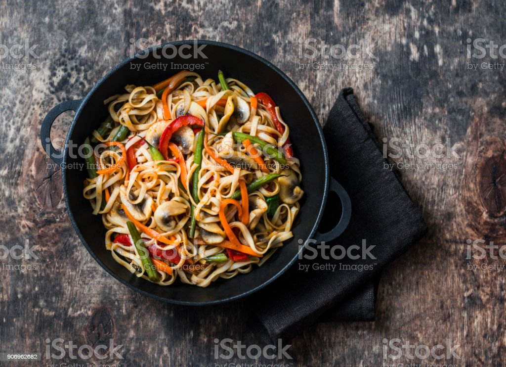 One pan yaki udon noodles with stir fry vegetables. Vegetarian noodles with green beans, sweet peppers, mushrooms, carrots - healthy foods for lunch on a wooden background, top view stock photo