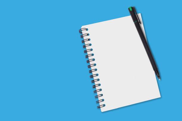 jeden papierowy notatnik ze spoiwem spiralnym i pustymi arkuszami w pobliżu czarnego plastikowego pióra leży niebieski stół biurowy. widok z góry. skopiuj miejsce na tekst. pojęcie biznesu lub edukacji - notes zdjęcia i obrazy z banku zdjęć