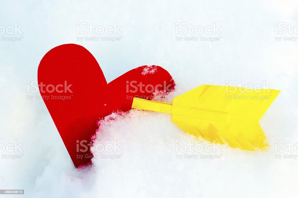 One paper red heart shape with arrow in the snow royalty-free stock photo