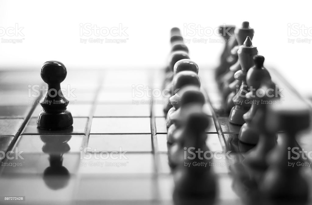 One pawn staying against full set of chess pieces. royalty-free stock photo