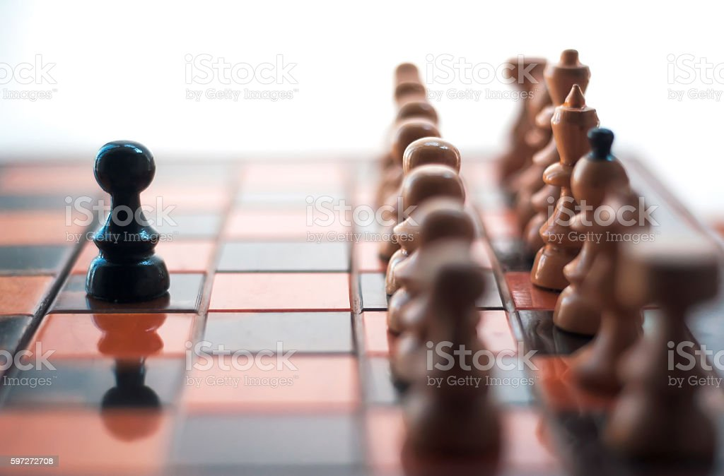 One pawn staying against full set of chess pieces. photo libre de droits