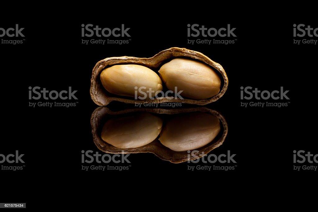 One peeled peanut isolated on black reflective background photo libre de droits