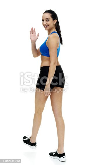 One person / full length / rear view / back / looking at camera of 18-19 years old adult beautiful black hair / ponytail / long hair caucasian female / young women athlete / sportsperson walking in front of white background wearing sports clothing / sports bra / bra / shorts / sports shoe who is happy / cheerful and greeting / showing hand raised / arms outstretched