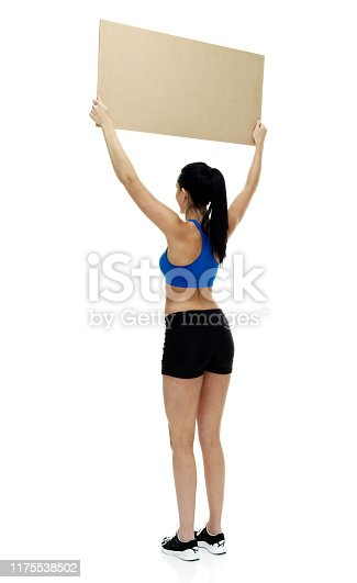 istock One person / full length / rear view / back of 18-19 years old adult beautiful black hair / long hair / ponytail caucasian female / young women athlete / sportsperson standing in front of white background who is happy / cheerful who is showing 1175538502