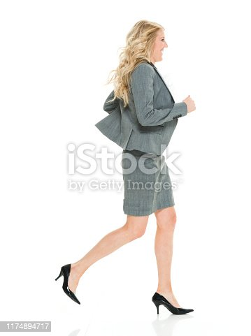 One person / full length / side view / profile view of 20-29 years old adult beautiful blond hair caucasian young women / female business person / businesswoman / manager running / jogging / exercising in front of white background wearing skirt / a suit who is smiling / happy / cheerful