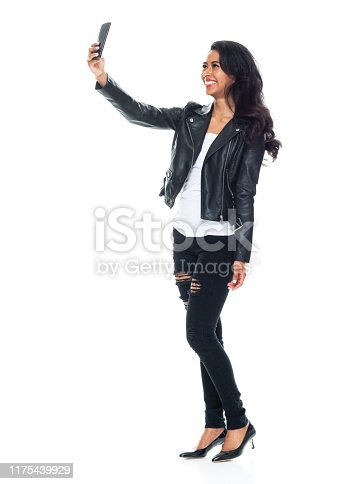One person / full length / side view / profile view of 20-29 years old adult beautiful / long hair latin american and hispanic ethnicity female / young women standing in front of white background wearing leather jacket / jeans who is smiling / happy / cheerful who is taking a selfie / photographing and holding mobile phone / using smart phone / torn
