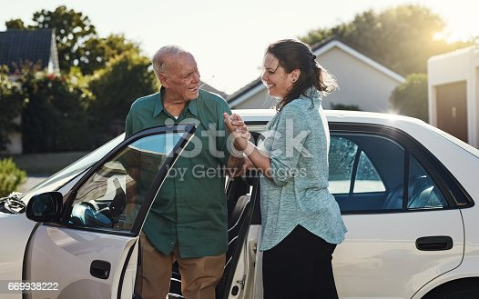 Shot of a woman helping her senior father out the car
