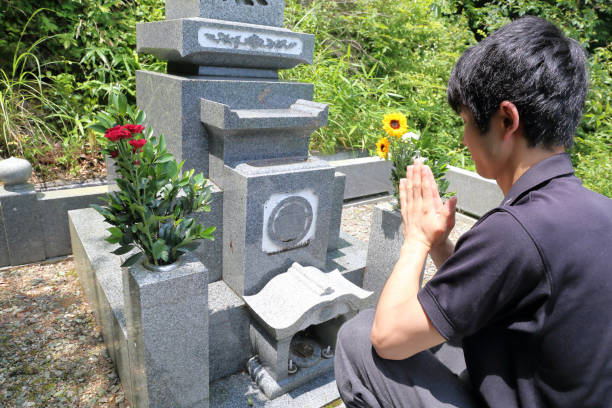 One person in front of a gravestone stock photo