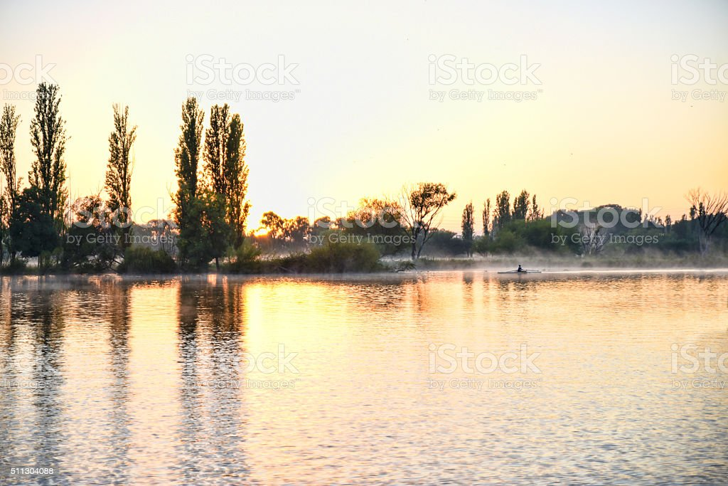 One person is rowing at sunrise on lake Burley Griffin stock photo