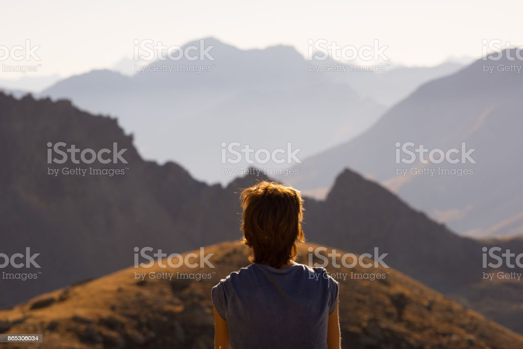 One person looking at view high up on the Alps. Expasive landscape, idyllic view at sunset. Rear view. stock photo