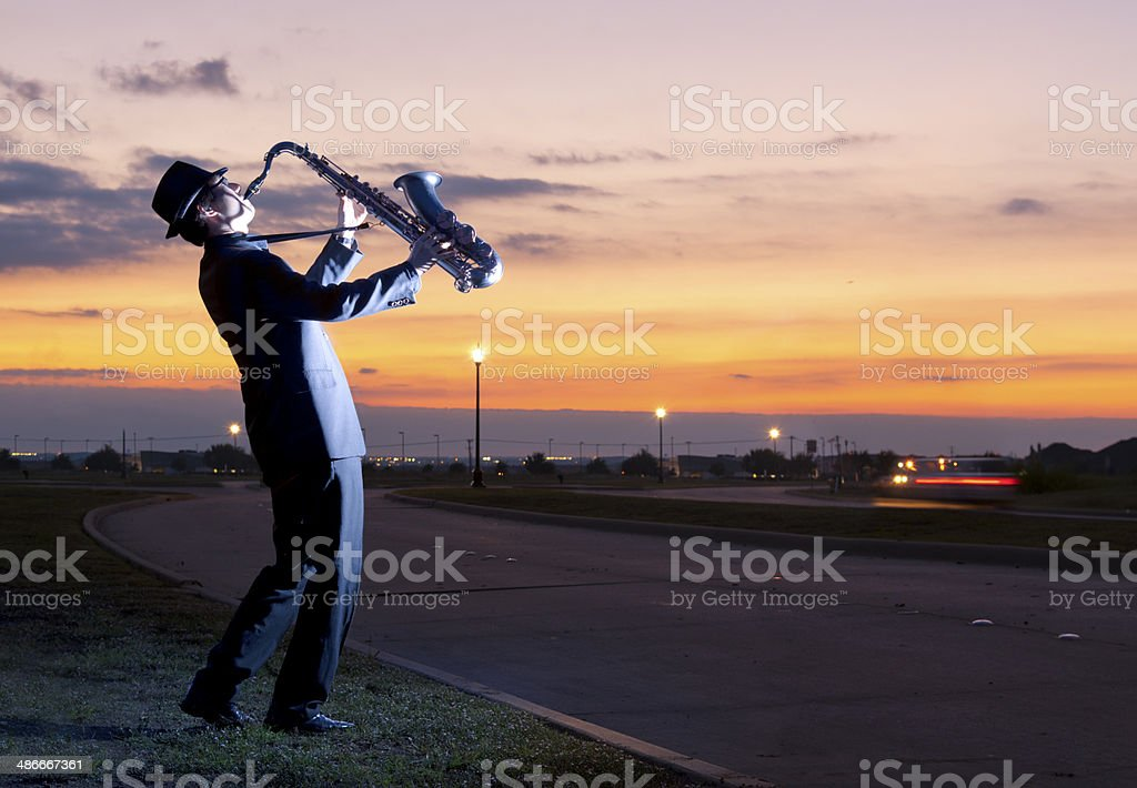 One person playing a saxophone beside Street Lamp stock photo