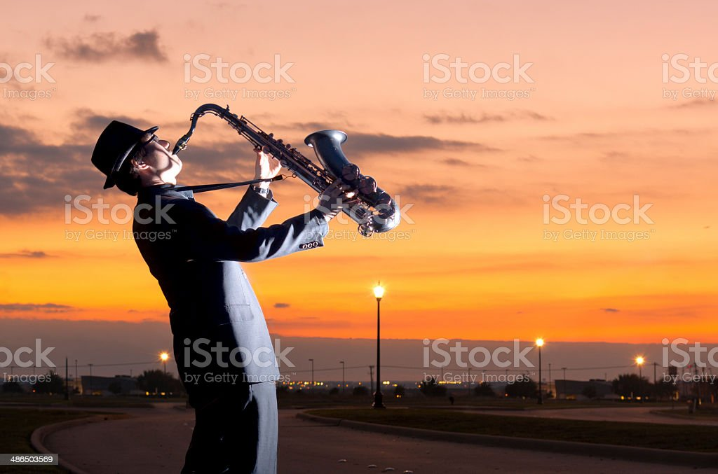 One person playing  a saxophone in the roadside stock photo