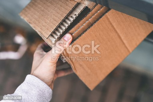 Close ups of a man in Sweden recycling used and broken household materials into a industrial garbage container.