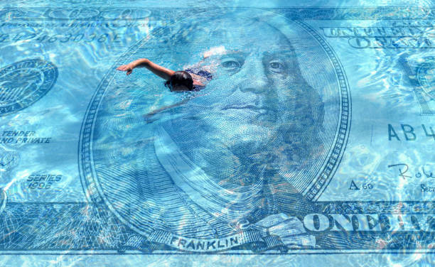 one person swimming on clear blue water covered with hundred dollar bill stock photo