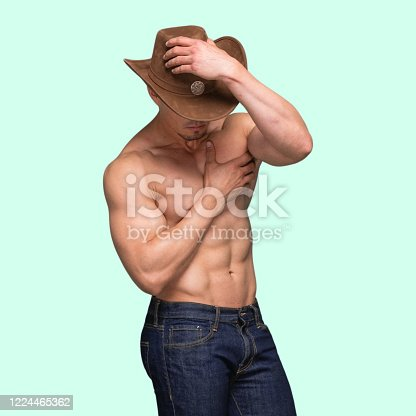 One person / waist up / front view of aged 20-29 years old latin american and hispanic ethnicity male / young male cowboy wearing jeans / pants / cowboy hat / hat who is a sex symbol / of muscular build / shirtless