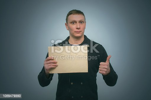 Man is holding in hands and is showing a blank wooden board with copy space and thumbs up gesture sign isolated on blue background.
