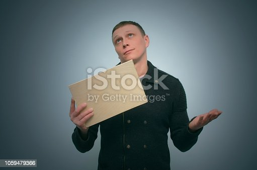 Man is holding in hands and is showing a blank wooden board with copy space isolated on blue background. Obvious solution concept.